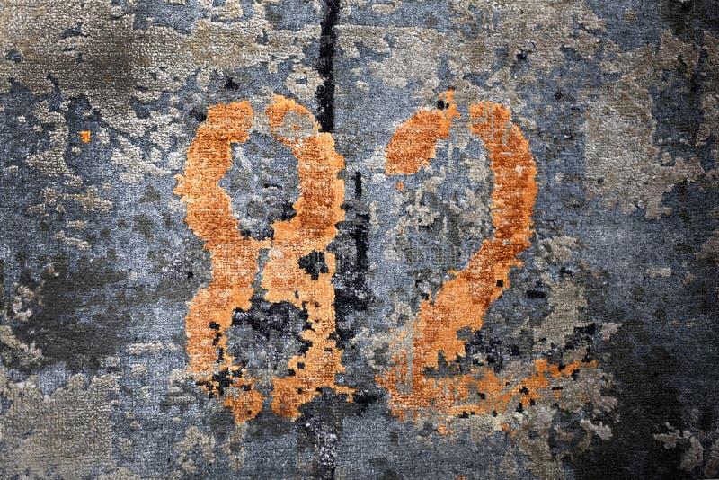 Número oxidado del color 82 en superficie azul áspera imagen de archivo