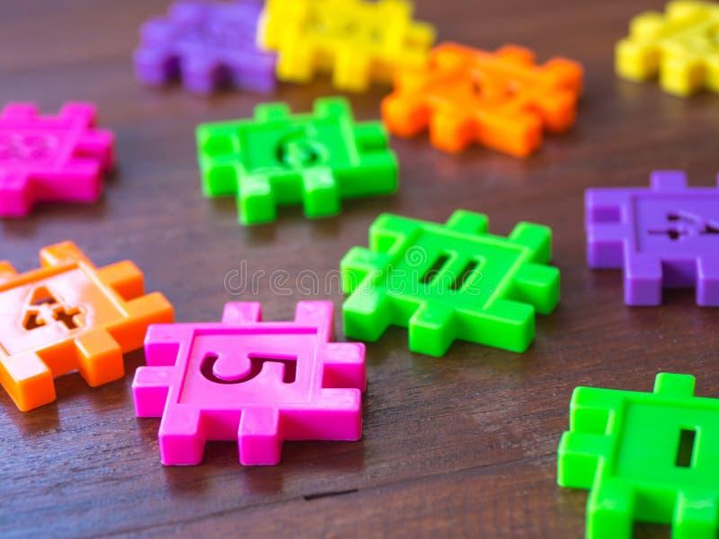Número plástico da serra de vaivém colorida do enigma na tabela de madeira Conceito da aprendizagem da educação e da matemática imagens de stock