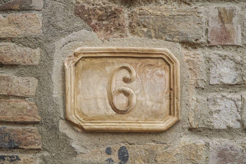 Número seis en una pared imagenes de archivo