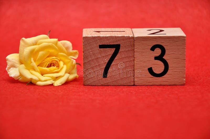 Número setenta y tres con una rosa amarilla foto de archivo libre de regalías