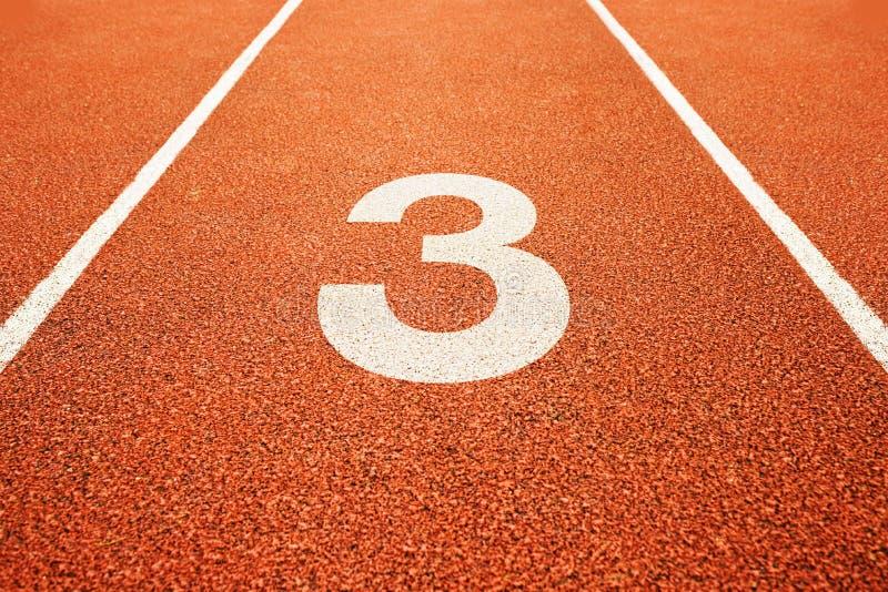 Número três na pista de atletismo imagens de stock
