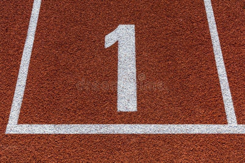 Número um na pista de atletismo para qualquer tempo do atletismo foto de stock