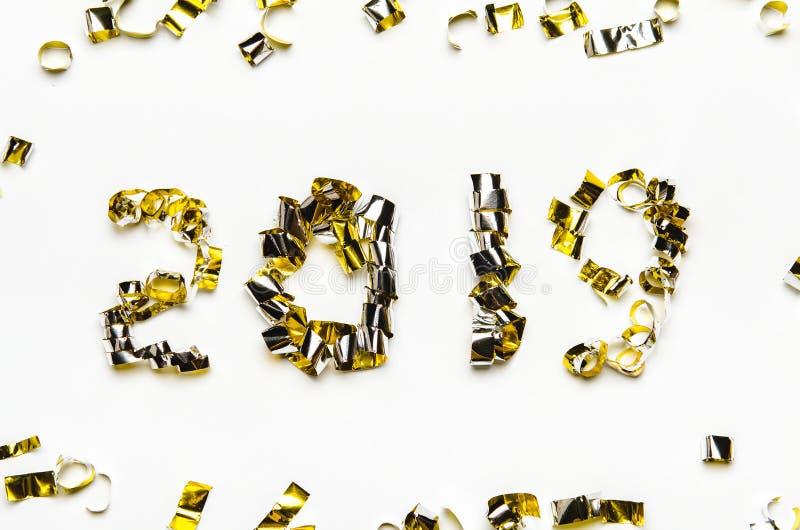 Números de oro de cinta del confeti y de la hoja El Año Nuevo 2019 en el fondo blanco imagen de archivo