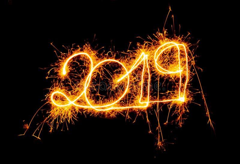 Números de oro de la Feliz Año Nuevo 2019 escritos con los fuegos artificiales de la chispa aislados en fondo negro fotografía de archivo libre de regalías