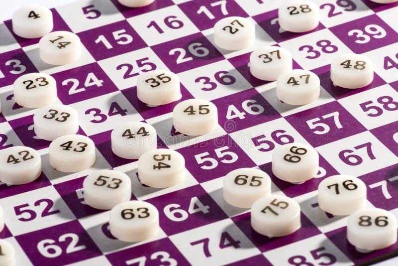 Números plásticos do Bingo sobre o cartão de jogo imagens de stock