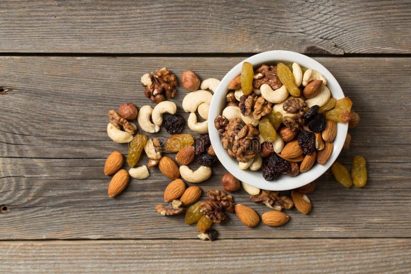 Nüsse und Trockenfrüchte in einer weißen Schüssel auf einem Holztisch lizenzfreie stockfotografie