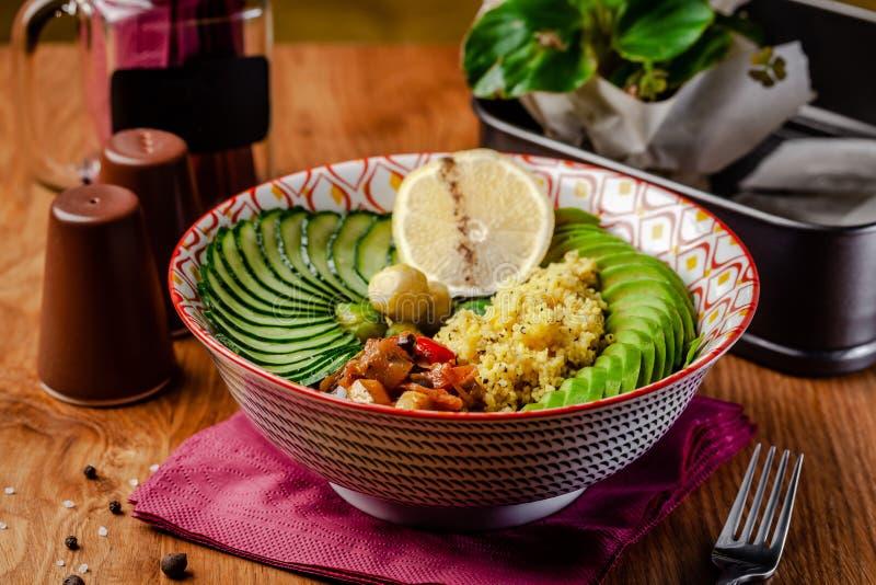 Nützliche italienische Nahrung des strengen Vegetariers Vegetarische Schüssel zum Frühstück von Breikuskus, von Avocado, von Gurk stockfotografie