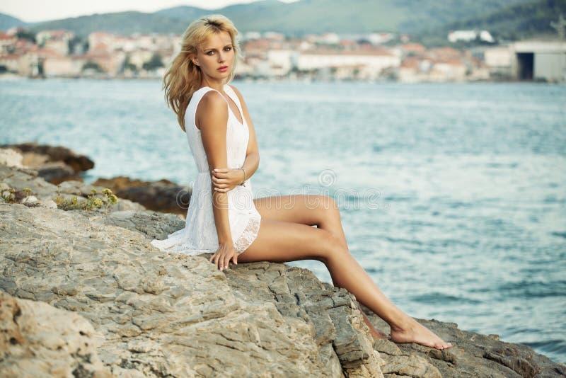 Nęcąca kobieta na skalistej plaży obraz royalty free