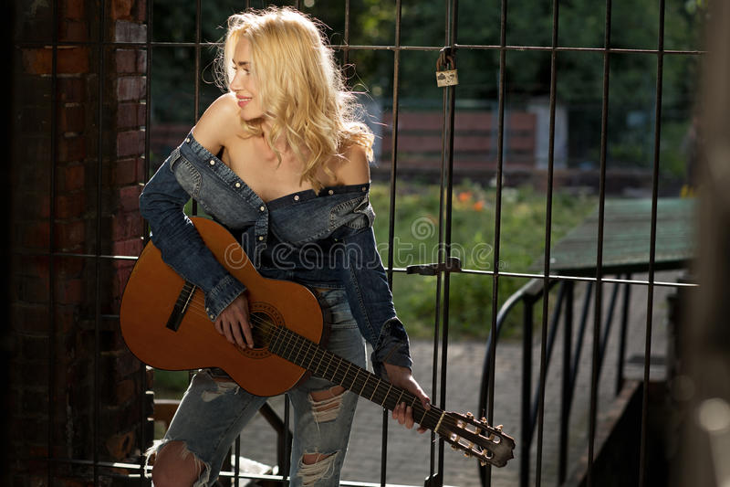 Nęcący blond wykonawca bawić się gitarę fotografia royalty free