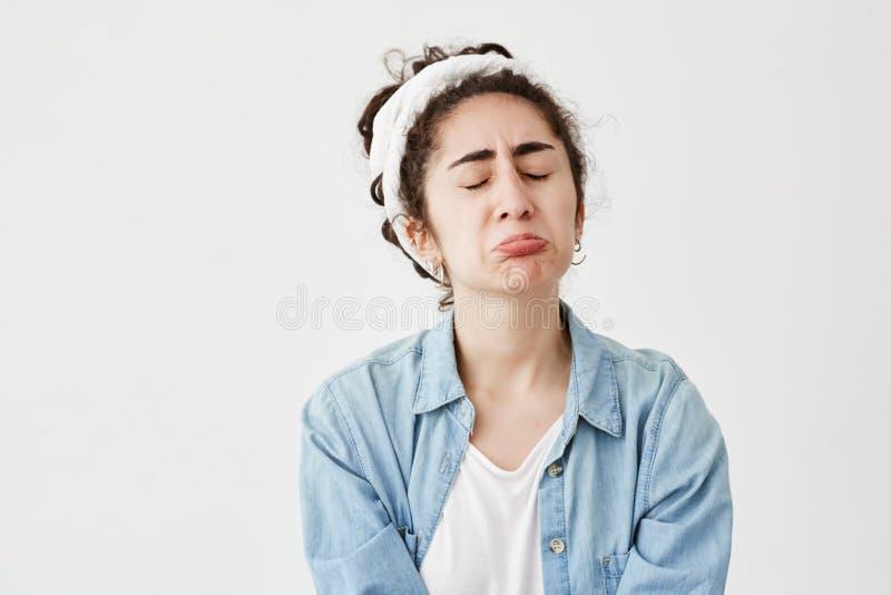 Nędzna wzburzona ponura kobieta z zmroku i falistego włosy spojrzeniami obrażającymi, pouts wargi, marszczy brwi twarz w rozpaczu obraz stock