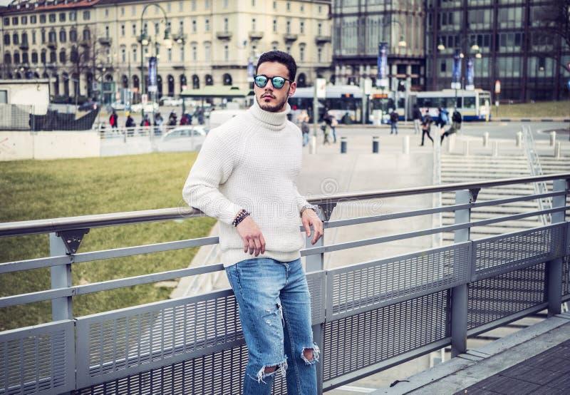 ??n aantrekkelijke mens in stad die het dragen van witte sweater plaatsen royalty-vrije stock foto's