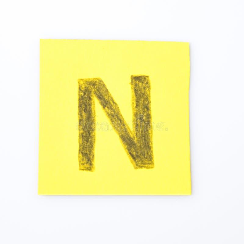 N abecadła listu handwrite na żółtym papierze fotografia stock
