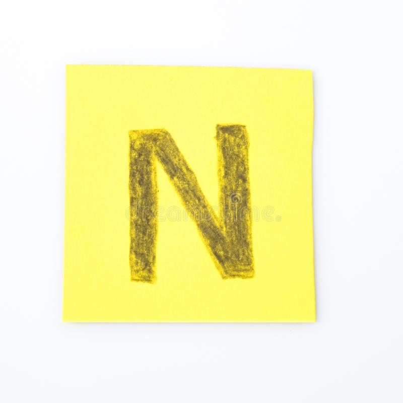 N alphabet letter handwrite on a yellow paper. Composition stock photography