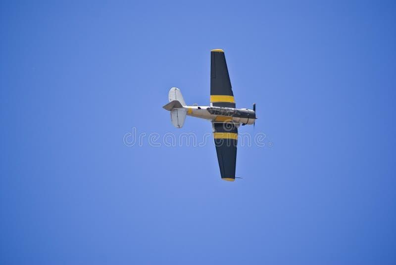 N. American AT-6C Harvard Mk 4. Vintage war plane - North American AT-6C Harvard Mk 4, executing a low altitude flyover, Barrel Roll maneuver royalty free stock image