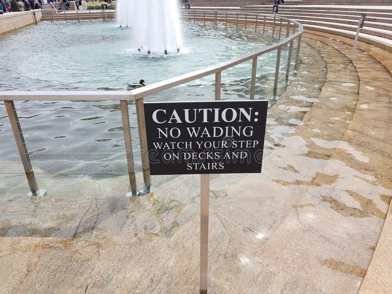 N'avertissez aucun patauger pour observer votre étape sur des plate-formes et les escaliers signent et fontaine photographie stock libre de droits