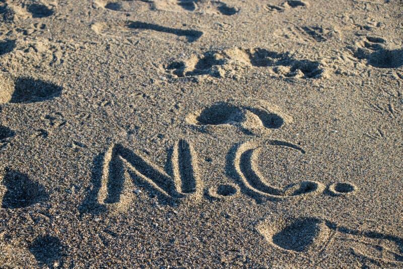 N C geschreven in het zand bij het strand stock foto's