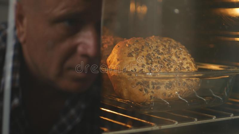 n a cozinha que cozinha o pão fresco e que olha no forno imagens de stock