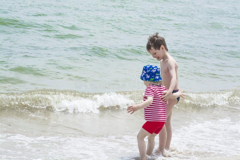 N el muchacho de la playa que ayuda al pequeño hermano a venir más cercano a la onda, imágenes de archivo libres de regalías