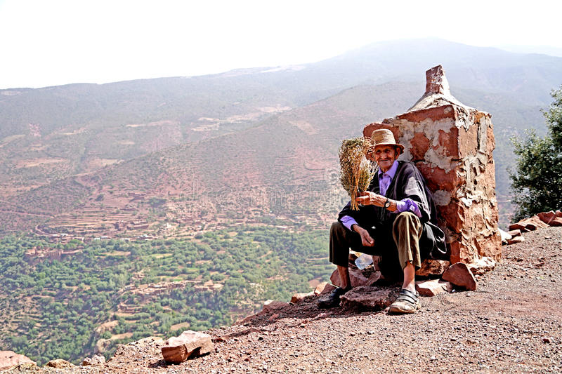 Old man medical herb salesman on the highway of the atlas mountains in Morocco stock image
