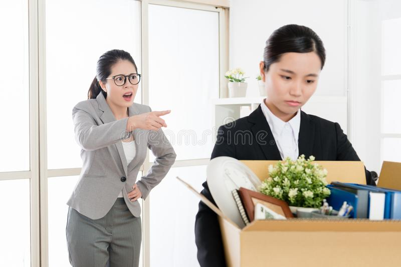 N employee scolded by the mean boss. Asian employee scolded by the mean boss and leaving the office carrying her stuffs with helpless and low spirit royalty free stock photos