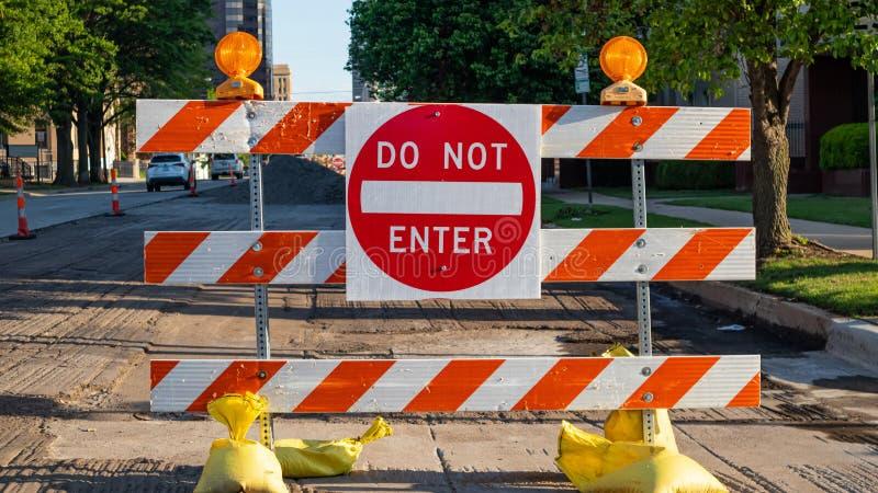 N'entrez pas, des courses sur route Le panneau routier, texte n'entrent pas et des barrières, fond urbain image libre de droits