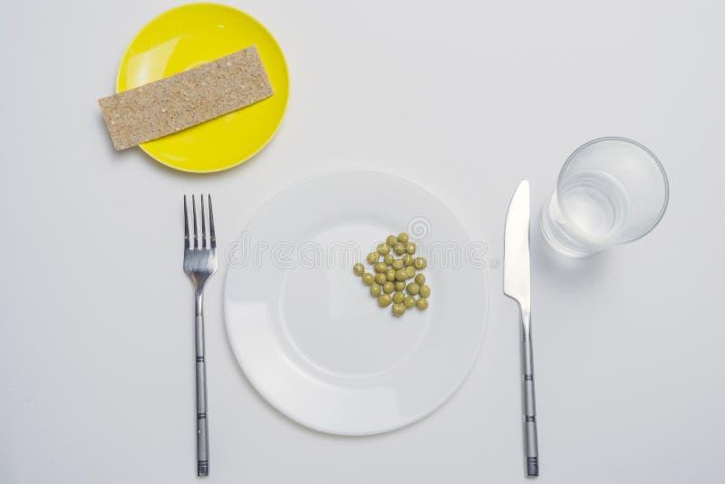 N?hren Sie Konzept Erbse auf einer leeren weißen Platte mit Messer und Gabel stockfoto