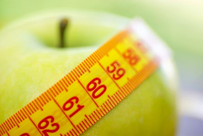 N?hrendes Konzept Gr?ner Apfel mit messendem Band Eignungs-und Gewichts-Verlust-Konzept lizenzfreies stockfoto