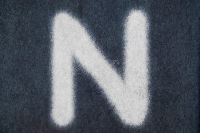 N isolerad kritabokstav i svart tavlabakgrund royaltyfri bild