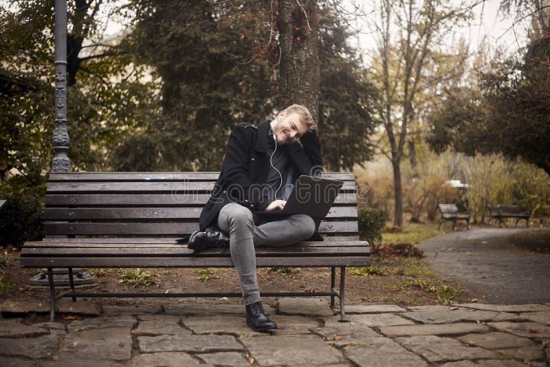 ??n jongelui glimlachen en gelukkige mens, die op bank in openbaar park zitten, die laptop met behulp van, royalty-vrije stock fotografie