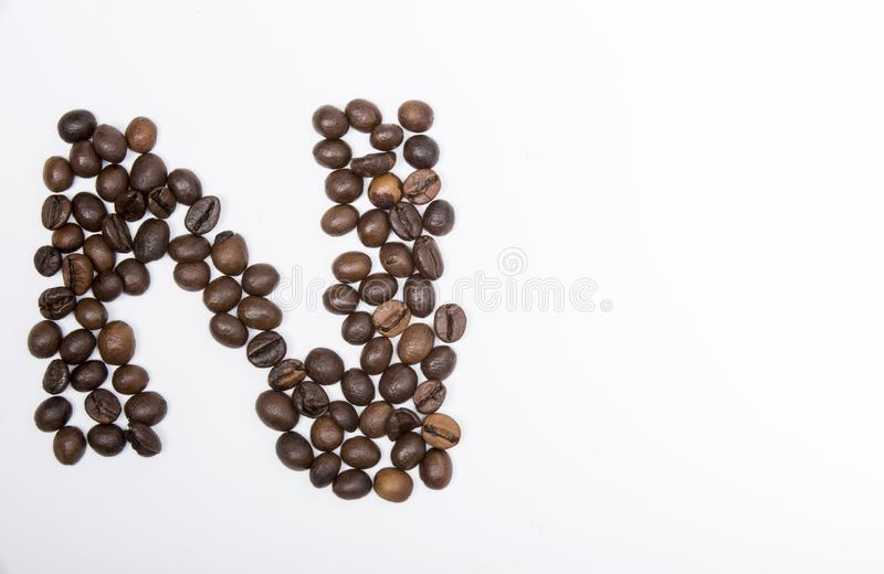N - large letter of english alphabet. Made up of unmolished roasted coffee beans on a white background royalty free stock images