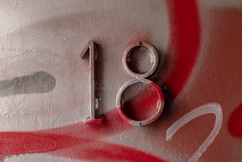 N?mero dieciocho Etiqueta 18 con la pintada urbana de la puerta Mayor?a de la edad imagen de archivo
