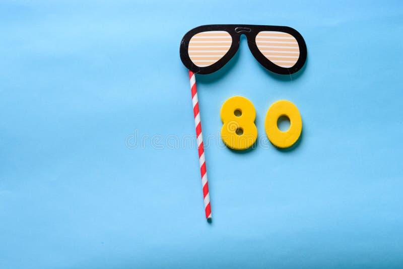 N?mero puesto plano de la visi?n superior y m?scara de papel linda del carnaval de las gafas de sol fotografía de archivo