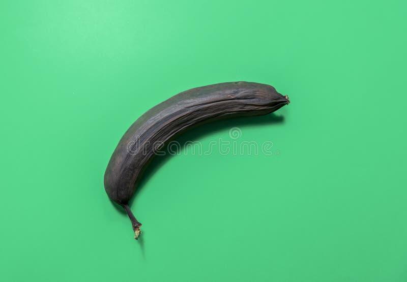 ??n overrijpe die banaan op groene achtergrond wordt ge?soleerd stock foto