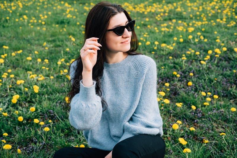 N?ra ?vre st?ende av den h?rliga millennial unga kvinnan i solglas?gon som sitter p? ?ng med blommor och gr?s f?r gul kamomill in royaltyfri bild