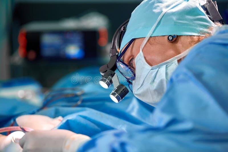 N?ra ?vre st?ende av den kvinnliga kirurgdoktorn som b?r den skyddande maskeringen och hatten under operationen Sjukv?rd l?karund royaltyfri foto