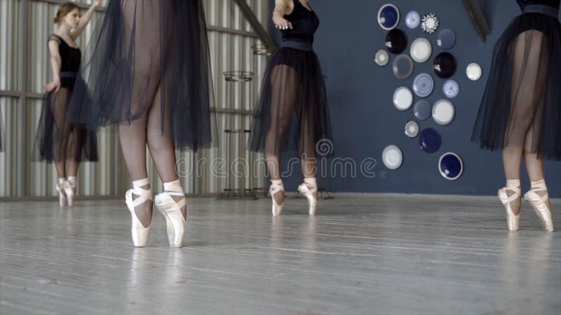 N?rbild av ballerina som dansar i svarta kl?nningar och den vita pointeskon actinium Ballerina f?rbereder sig f?r balett och dans arkivbilder