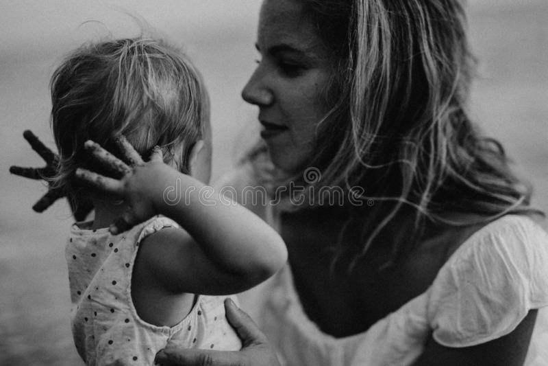 N?rbild av den unga modern med en litet barnflicka p? stranden p? sommarferie royaltyfri fotografi