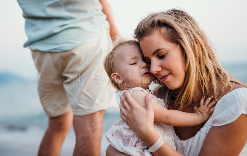 N?rbild av den unga modern med en litet barnflicka p? stranden p? sommarferie arkivbild