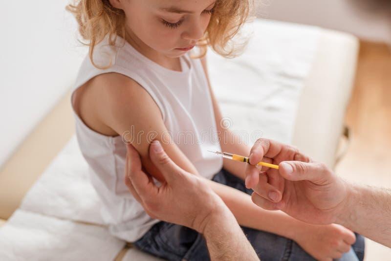 N?rbild av en blond pojke och en doktor med en injektionsspruta royaltyfria bilder