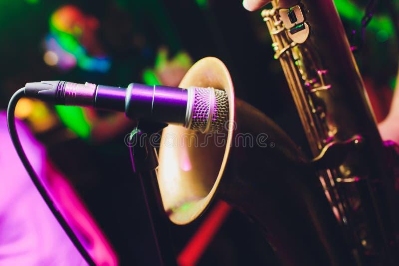 N?rbild av en saxofonist som spelar hans instrument, en saxofon, bredvid en mikrofon med sockeln Svart bakgrund arkivbild