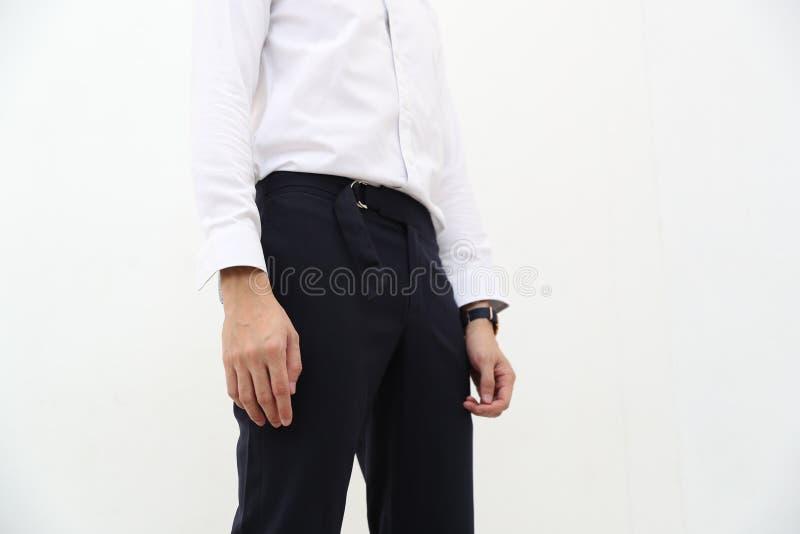 N?rbild av en stilig man i den vita formella skjortan och svart l?ng byxa royaltyfria bilder