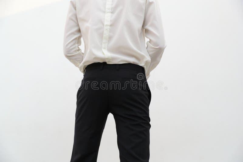 N?rbild av en stilig man i den vita V-ringningskjortan och svart l?ng byxa fotografering för bildbyråer