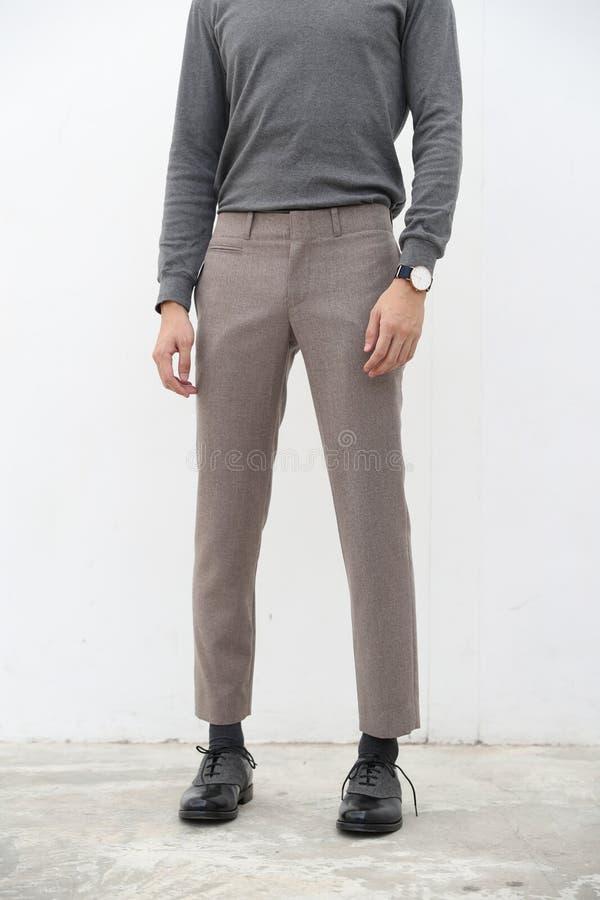 N?rbild av en stilig man i gr? halvpolokrageskjorta och l?ng byxa p? vit bakgrund arkivbilder
