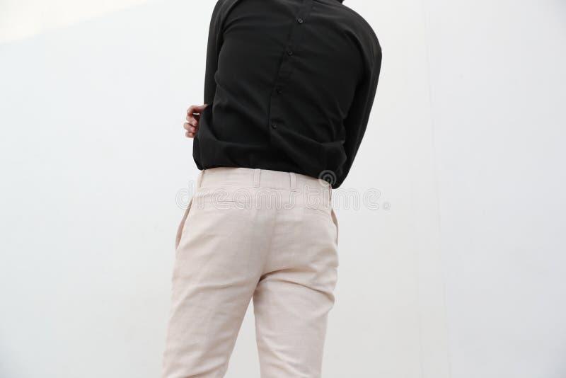 N?rbild av en stilig man i svart V-ringningskjorta och vit l?ng byxa arkivfoton