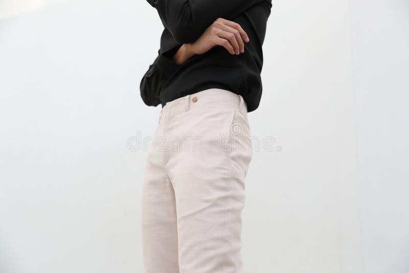 N?rbild av en stilig man i svart V-ringningskjorta och vit l?ng byxa fotografering för bildbyråer