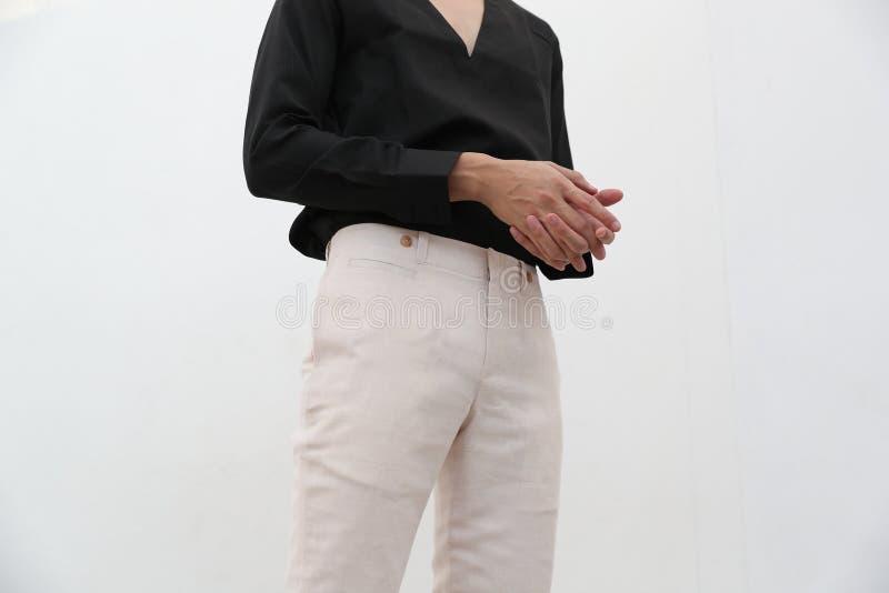 N?rbild av en stilig man i svart V-ringningskjorta och vit l?ng byxa royaltyfri foto