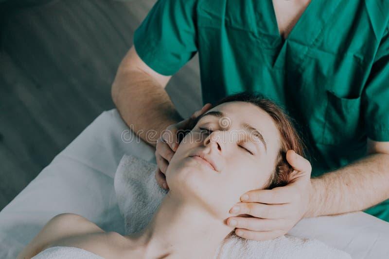 N?rbild av en ung kvinna som f?r Spa behandling Manliga händer gör huvudmassage till en härlig ung kvinna arkivfoton