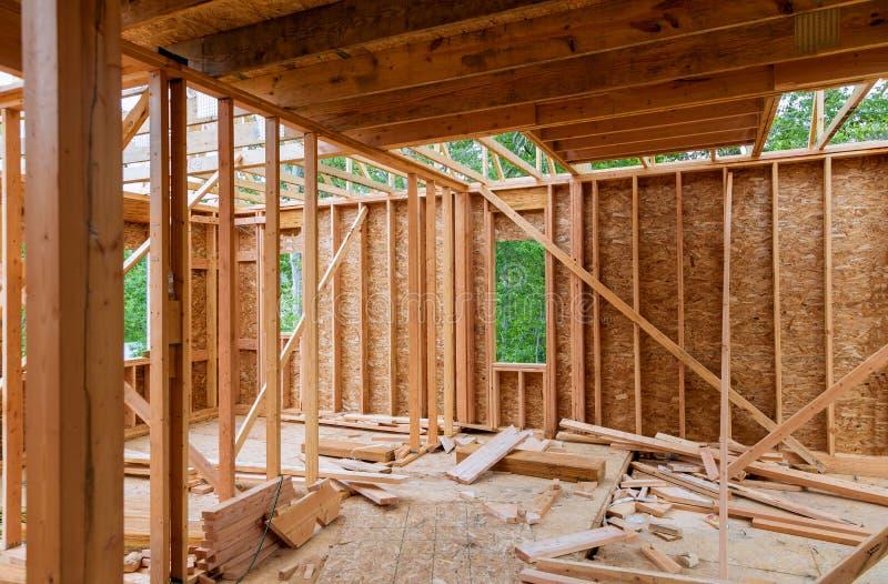 N?rbild av str?len som hem byggs under konstruktion och bl? himmel med den tr?br?ckband-, stolpe- och str?lramen Timmerramhus som arkivbild