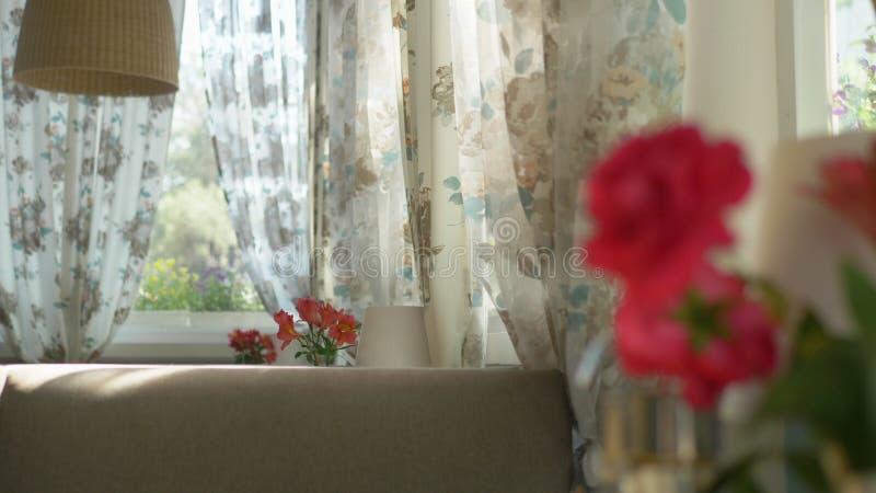 N?rbild En gullig bukett av r?da rosor och freesia i en vas p? en tabell p? en solig sommardag i ett kaf? ?verf?ring av arkivbilder