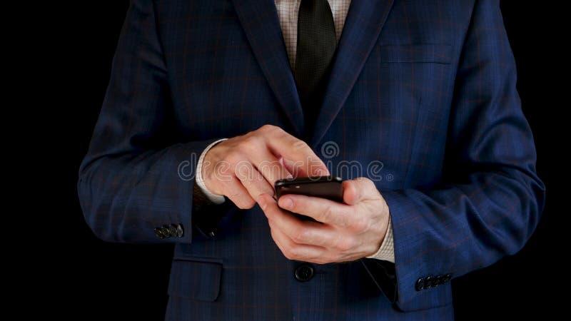 N?rbild En manlig aff?rsman i en h?rlig dr?kt arbetar genom att anv?nda en smartphone som trycker p? peksk?rmen fotografering för bildbyråer